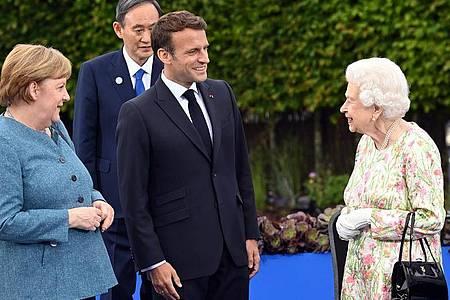Die britische Königin Elizabeth II. (r) mit Angela Merkel (l-r), Yoshihide Suga, Premierminister von Japan, und Emmanuel Macron. Foto: Karwai Tang/G7 Cornwall 2021/dpa