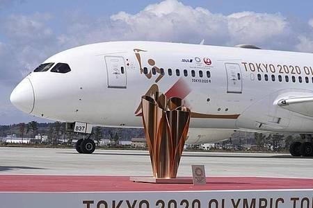 Ein Flugzeug mit dem olympischen Feuer ist auf der Matsushima-Basis nördlich von Tokio gelandet. Foto: Eugene Hoshiko/AP/dpa