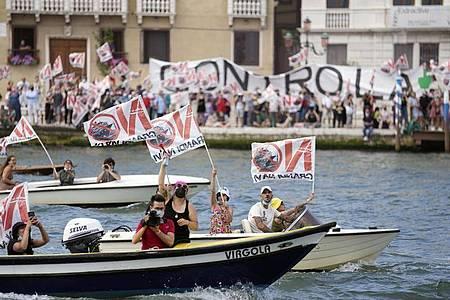 Aktivisten protestieren gegen den Start des ersten Kreuzfahrtschiffs in Venedig. Foto: Antonio Calanni/AP/dpa