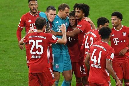 Die Münchner Mannschaft um Kapitän Manuel Neuer feiert den hart erkämpften 3:2 Sieg. Foto: Andreas Gebert/Reuters/Pool/dpa