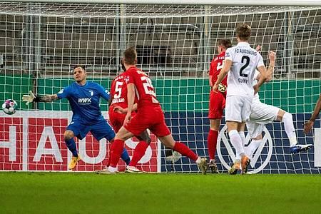 Willi Orban (M) köpft den Ball zur Leipziger Führung ins Tor. RB setzte sich souverän in Augsburg durch. Foto: Stefan Puchner/dpa