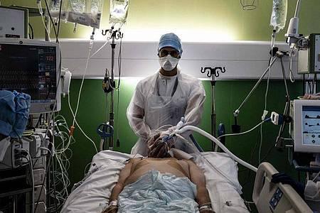 Ein medizinischer Angestellter (M) kümmert sich auf der Intensivstation eines Krankenhauses in Pierre-Benite um einen Corona-Patienten. Foto: Jeff Pachoud/AFP/dpa