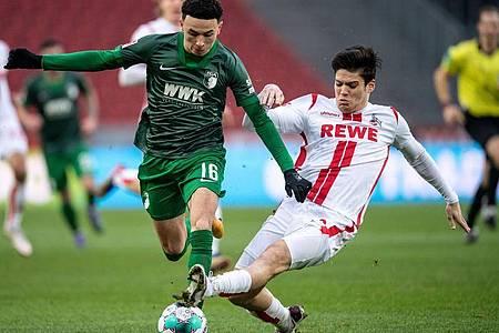 Kölns Jorge Mere (r) kämpft mit Augsburgs Ruben Vargas um den Ball. Foto: Marius Becker/dpa