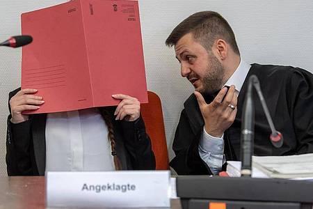 Die Angeklagte Jennifer W. hält im Gerichtssaal einen roten Aktendeckel vor das Gesicht. Rechts neben ihr sitzt Anwalt Ali Aydin. Foto: Peter Kneffel/dpa