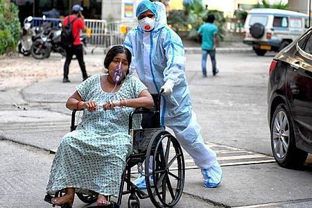 Eine mit dem Coronavirus infizierte Patientin sitzt im Rollstuhl und wird in das Kolkata Medical College Hospital eingeliefert. Foto: Avishek Das/SOPA Images via ZUMA Wire/dpa