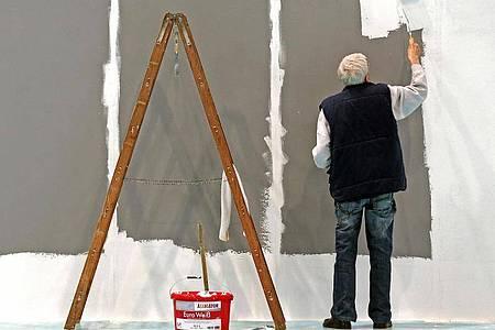 Ein älterer Mann streicht auf der Leipziger Messe eine Wand. Die Menschen in Deutschland beziehen immer länger Rente, zugleich sind sie in den vergangenen Jahren immer später in Rente gegangen. Foto: Jan Woitas/dpa-Zentralbild/dpa