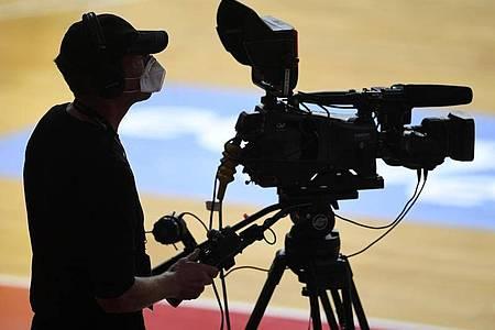 Ein Kameramann steht mit Mundschutz bei einem Basketballspiel an seiner TV-Kamera. Foto: Andreas Gebert/Reuters-Pool/dpa