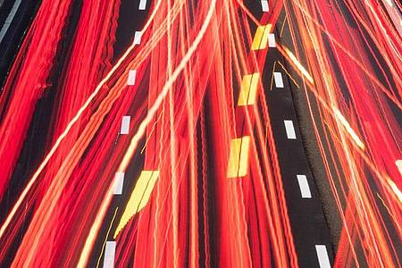 Die Scheinwerfer vorbeifahrender Fahrzeuge ziehen auf einer Autobahn ihre Lichtspuren durch die hereinbrechende Dunkelheit (Aufnahme mit Langzeitbelichtung). Foto: Boris Roessler/dpa