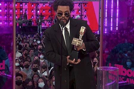 The Weeknd zeigt seinen Top Artist Award. Foto: -/NBC/AP/dpa