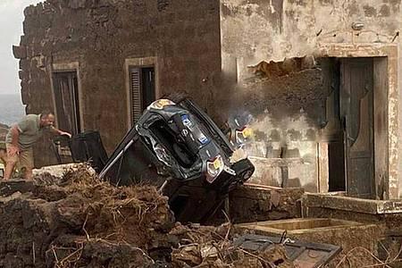 Ein zerstörtes Fahrzeug liegt abseits der Straße an einem Haus. Auf der italienischen Mittelmeerinsel Pantelleria sind zwei Menschen bei einem Unwetter ums Leben gekommen. Foto: Vigili del Fuoco/dpa