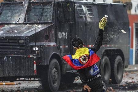 Ein Protestler wirft in einem Außenbezirk von Bogotá einen Farbbeutel auf ein Polizeifahrzeug. Foto: Ivan Valencia/AP/dpa