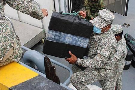 Auf diesem von der kolumbianischen Armee zur Verfügung gestellten Bild entladen Soldaten beschlagnahmte Drogen aus einem Halbtaucher. Foto: ---/Armada de Colombia/dpa