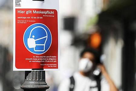 Ein Schild mit der Aufschrift «Hier gilt Maskenpflicht» hängt in der Fußgängerzone in Bonn. Erstmals seit drei Wochen liegt die 7-Tage-Inzidenz in Deutschland wieder höher als am Vortag. Foto: Oliver Berg/dpa