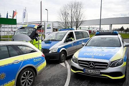 Fahrzeuge der Polizei stehen vor dem Werk eines Getränkeherstellers, wo eine Serie explosiver Postsendungen begannn. Jetzt wird wird einem 66-jährigen Elektriker der Prozess gemacht. Foto: Rene Priebe/dpa