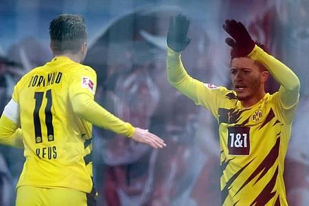 Dortmunds Jadon Sancho (r) jubelt mit Marco Reus über seinen Treffer zur 1:0-Auswärtsführung. Foto: Jan Woitas/dpa
