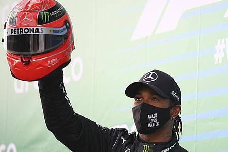 Lewis Hamilton zog mit seinem siebten Formel-1-WM-Titel mit Michael Schumacher gleich, dessen Helm erhielt er auf dem Nürburgring von dessen Sohn Nick. Foto: Bryn Lennon/Pool Getty/AP/dpa