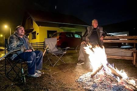 Zwei Männer sitzen neben einem Lagerfeuer, während sie aufgrund der Gefahr von Nachbeben die Nacht im Freien verbringen. Foto: Davor Puklavec/Pixsell/Xinhua/dpa
