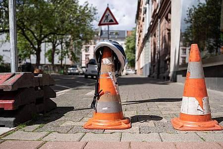Ein Polizei-Fahrradhelm iegt auf eine Pylone, die eine Straße im dicht besiedelten Frankfurter Nordend absperrt, nachdem dort bei Baggerarbeiten eine Weltkriegsbombe entdeckt wurde. Foto: Frank Rumpenhorst/dpa