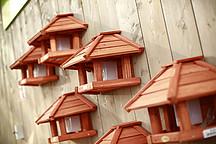 Fünf rote Vogelhäuschen an einer Holzwand