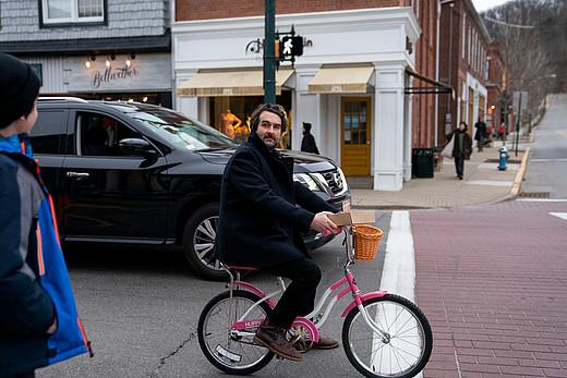 Der Protagonist von Die Professorin fährt ein rosanes Kinderrad über die Straße.