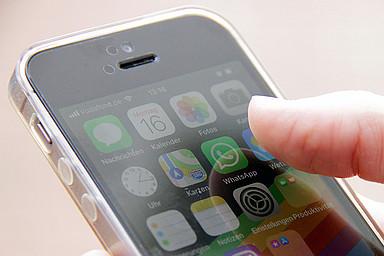 Person tippt auf das Whatsapp auf dem Smartphone
