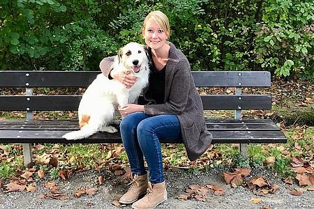 Mara und sitzt mit einem Hund auf einer Bank