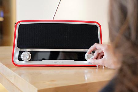 Frau schaltet Radio ein