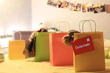 Roter Gutschein aus der Gutschein-Box hängt an einer Einkaufstüte
