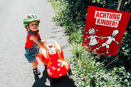 Junge mit Bobbycar neben Achtung Kinder-Plakat