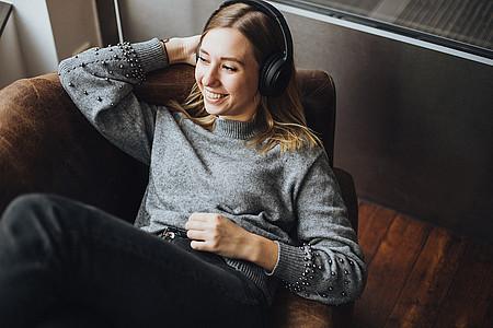 Frau liegt im Sessel und hört Webradio
