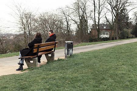 Junge Frauen mit Abstand auf einer Parkbank