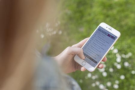 Frau klickt sich auf ihrem Smartphone durch die Radio Lippe App