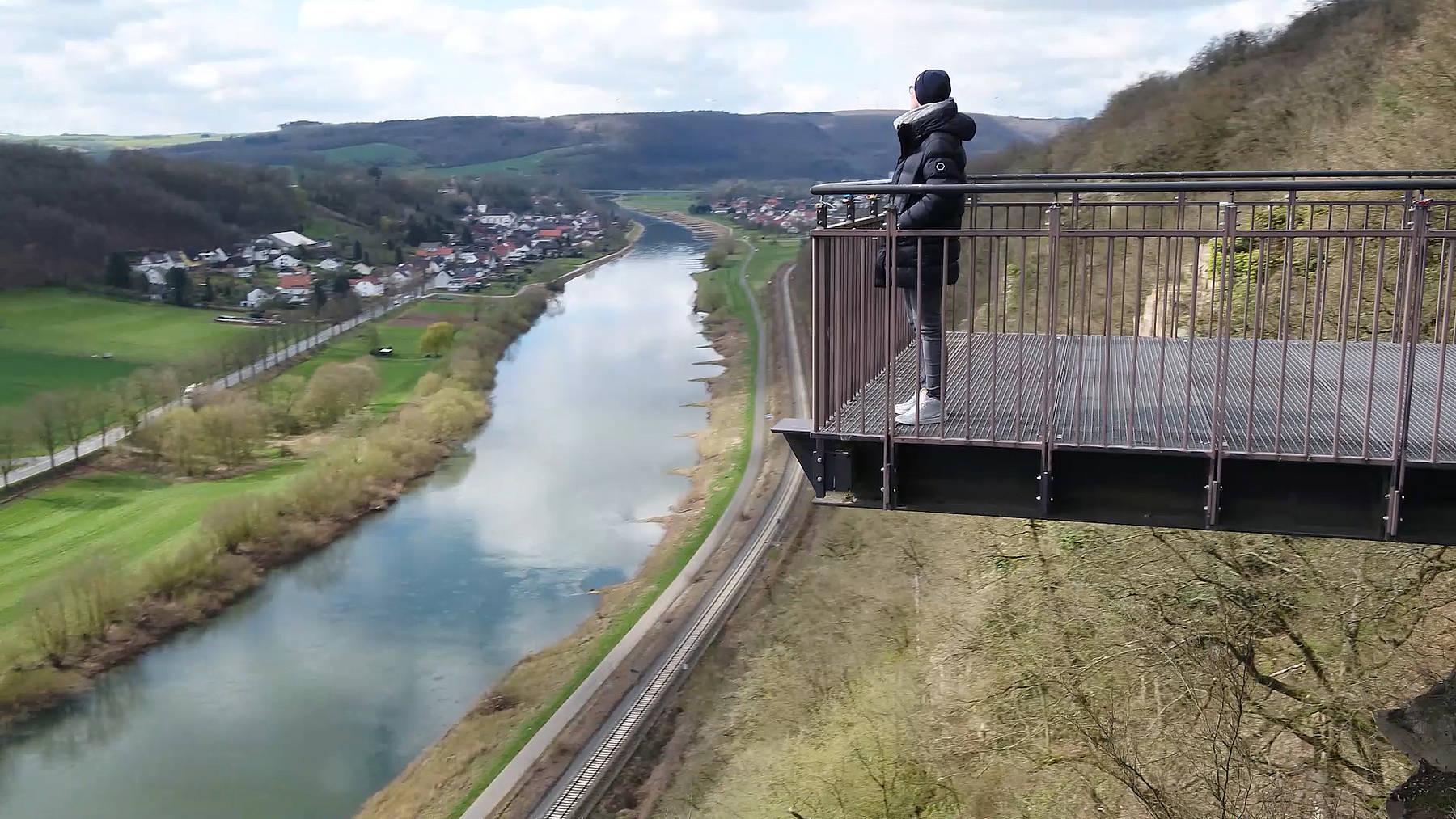 """Christina Huckle steht auf dem """"Weser-SkyWalk"""" und blickt auf die Weser"""